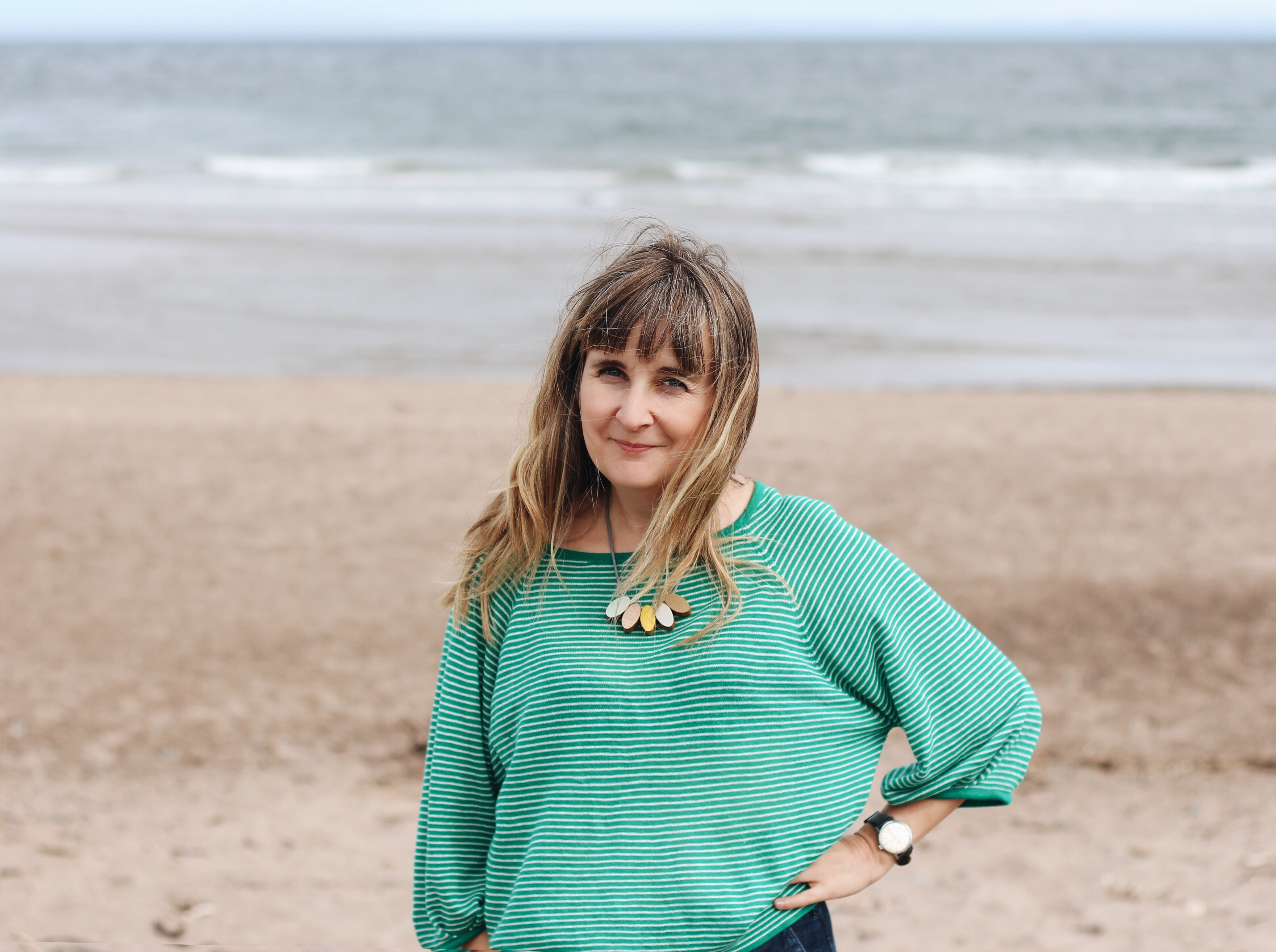 Illustrator Helen Stephens on a beach wearing a green jumper